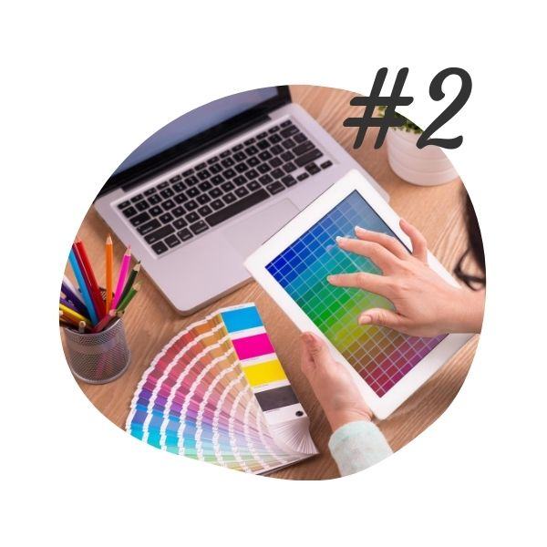 #2 - Design - woman with a laptop, working on a tablet with color scales from blue to green to yellow to red, colorful pencils in a wire cup, and a paint color fan