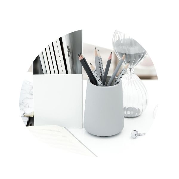 Desktop accessories in white and gray - magazines in a white holder, pencils in a gray cup, and an hourglass sand timer