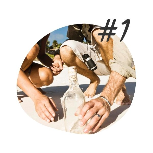 #1 - Discovery - man and woman holding hands, crouching on a sandy beach on a sunny day, reaching for a bottle seemingly washed up from the ocean