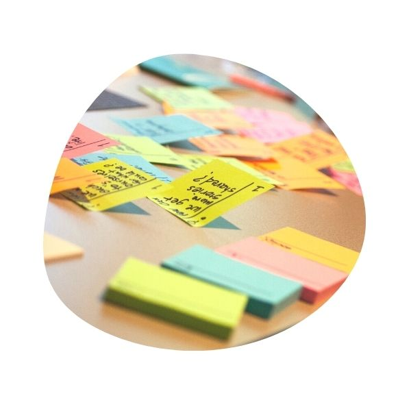 Desktop covered with colorful Post-its, most with ideas written on them