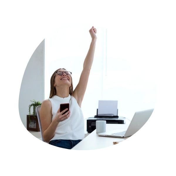 Smiling woman with open laptop on the desk, phone in hand, raising the other hand skyward in triumph