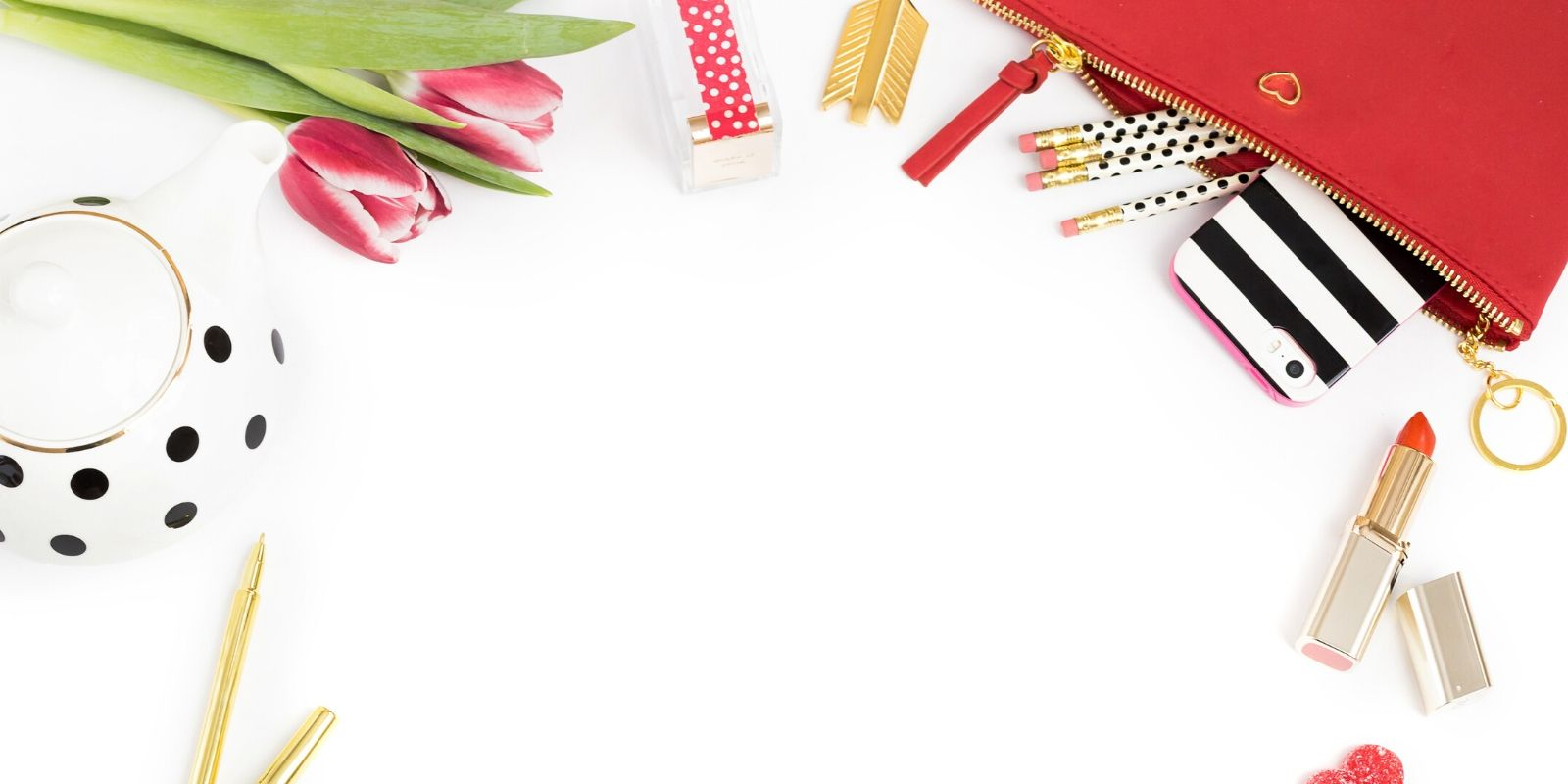 White desktop with red tulips, red pencil case, a cell phone with a black and white striped cover, red lipstick, and a polka dotted teapot
